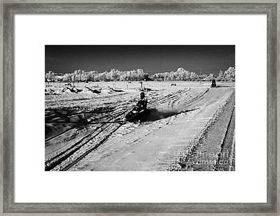two men on snowmobiles crossing frozen fields in rural Forget Saskatchewan Canada Framed Print by Joe Fox