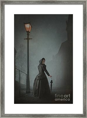 Victorian Woman Under Streetlamp In Fog Framed Print by Lee Avison