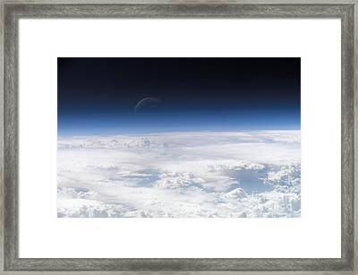 View Of The Crescent Moon Through The Top Of The Earths Atmosphere Framed Print by Paul Fearn