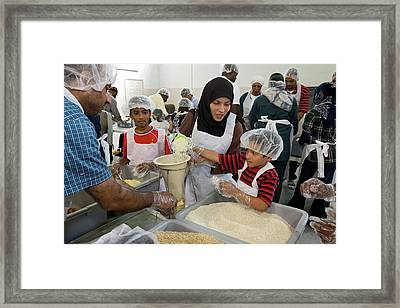 Volunteers Preparing Meal Packages Framed Print by Jim West
