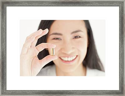 Woman Holding Capsule Framed Print by Ian Hooton