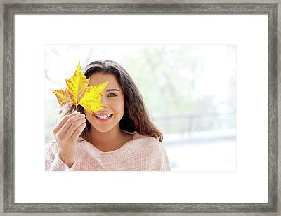 Woman Holding Leaf In Front Of Face Framed Print by Ian Hooton
