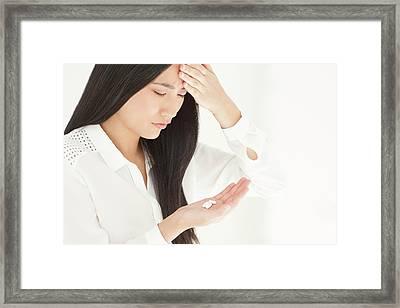 Woman Holding Tablets Framed Print by Ian Hooton