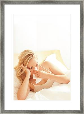 Woman In Bed Blowing Nose On Tissue Framed Print by Ian Hooton