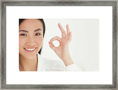 Woman Making Ok Sign Framed Print by Ian Hooton