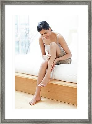 Woman Rubbing Her Leg Framed Print by Ian Hooton