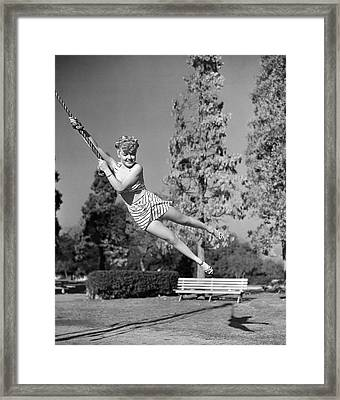 Woman Swinging On A Rope Framed Print by Underwood Archives