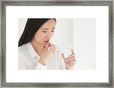 Woman Taking Painkiller Framed Print by Ian Hooton