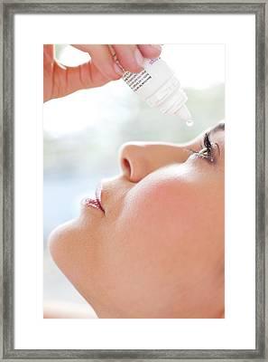 Woman Using Eye Drops Framed Print by Ian Hooton