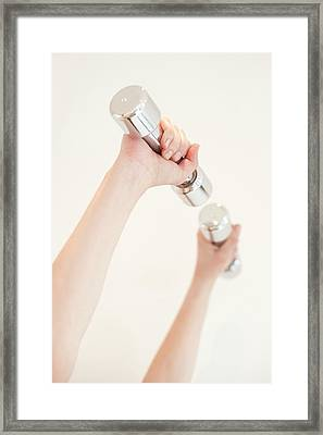 Woman Using Hand Weights Framed Print by Ian Hooton