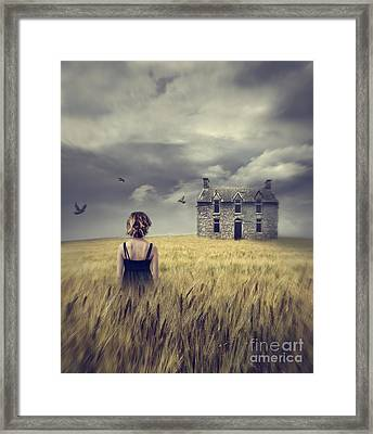 Woman Walking In Wheat Field With Abandoned House In Background Framed Print by Sandra Cunningham