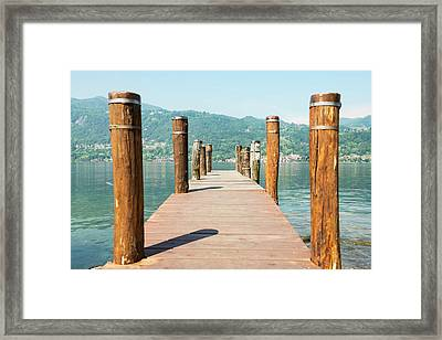 Wooden Dock And Posts On Lake Orta Framed Print by Mats Silvan