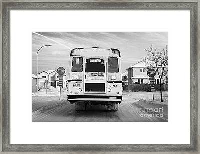 yellow school bus travelling through snow at stop sign Saskatoon Saskatchewan Canada Framed Print by Joe Fox