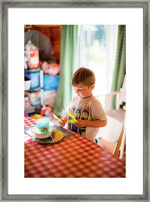 Young Boy Setting The Table At Home Framed Print by Samuel Ashfield