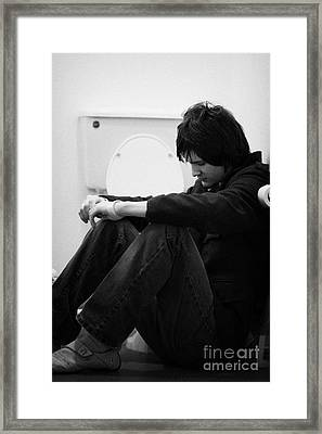 Young Dark Haired Teenage Man Sitting On The Floor Of The Bathroom With Back Against The Wall In The Framed Print by Joe Fox