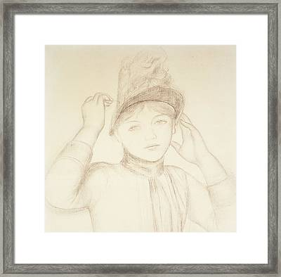 Young Woman Arranging Her Hat Framed Print by Pierre Auguste Renoir