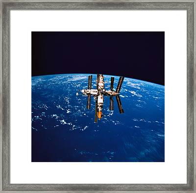 A Space Station In Orbit Above The Earth Framed Print by Stockbyte