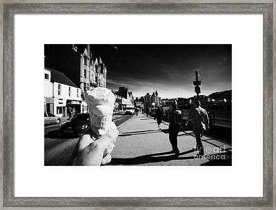 carrying an ice cream along the sea front in oban Scotland uk Framed Print by Joe Fox