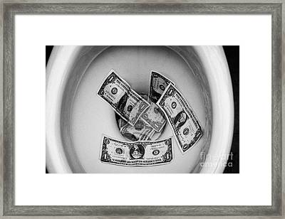 Flushing Us Dollar Bills Down The Toilet Framed Print by Joe Fox