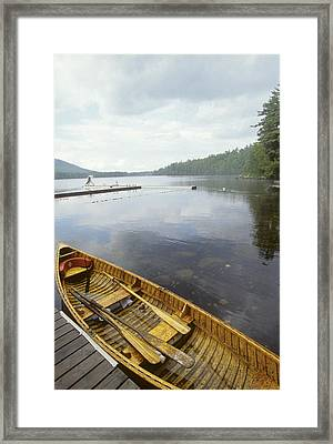A Canoe Floats Next To A Dock Framed Print by Skip Brown