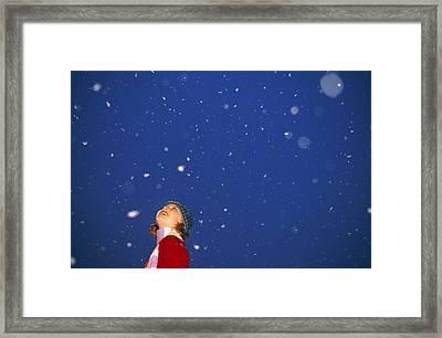 A Child Revels In Falling Snow Framed Print by John Burcham