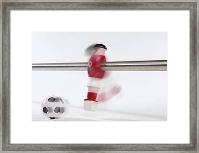 A Foosball Figurine Kicking A Soccer Ball, Blurred Motion Framed Print by Caspar Benson