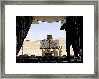 A Forklift Loads Cargo Onto A C-130 Framed Print by Stocktrek Images