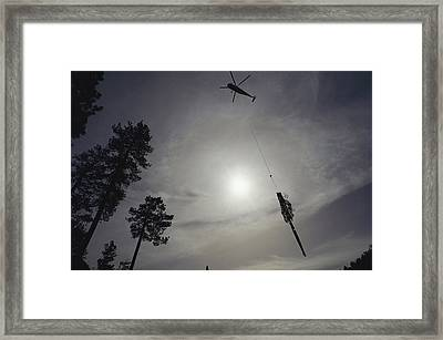 A Helicopter Lifts Cut Timber Framed Print by Joel Sartore