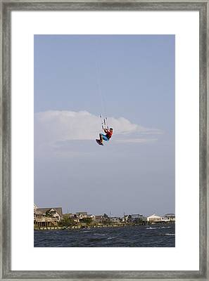 A Kiteboarder Jumps High Over Beach Framed Print by Skip Brown