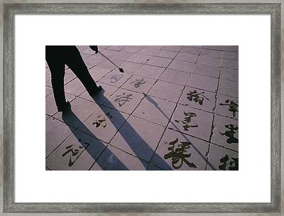 A Man Paints Chinese Calligraphy Framed Print by Justin Guariglia