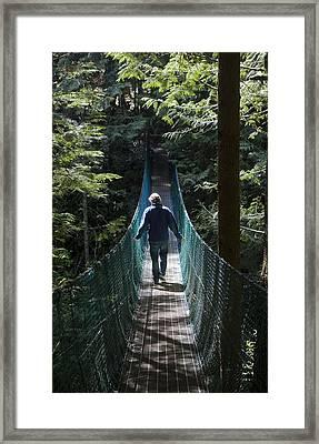 A Man Walks Across A Suspension Bridge Framed Print by Taylor S. Kennedy