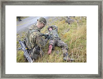 A Patrol Medic Applies First Aid Framed Print by Andrew Chittock