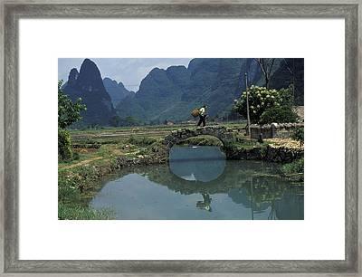 A Peasant Crosses A Stone Bridge Framed Print by Raymond Gehman