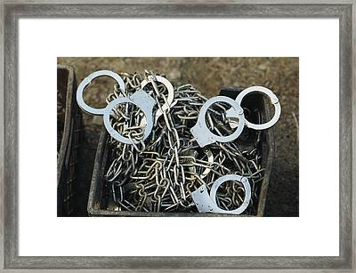 A Pile Of Chains And Handcuffs Framed Print by Bill Curtsinger