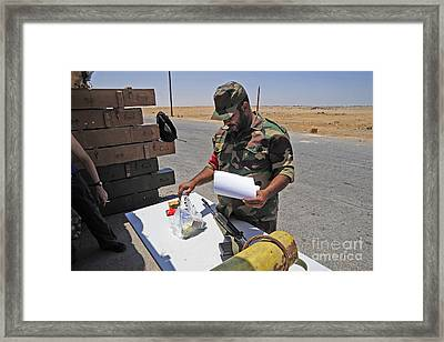 A Rebel Collects His Food Ration Framed Print by Andrew Chittock