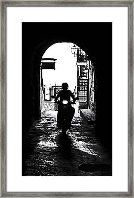 a scooter rider in the back light in a narrow street in Italy Framed Print by Joana Kruse