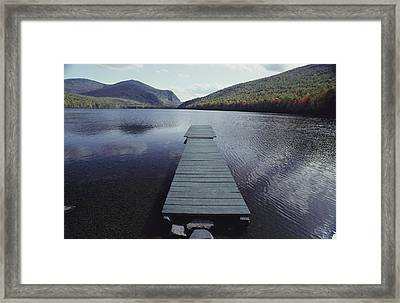 A Small Dock Leads Out To Placid Waters Framed Print by Bill Curtsinger