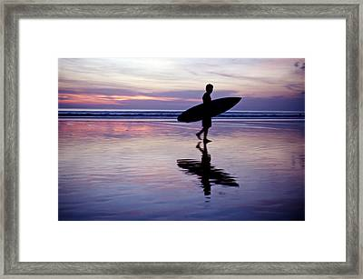 A Surfer Walks Across The Beaches Framed Print by Justin Guariglia