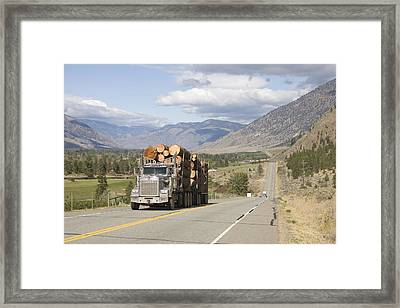 A Truck Carries Logs Down The Highway Framed Print by Taylor S. Kennedy