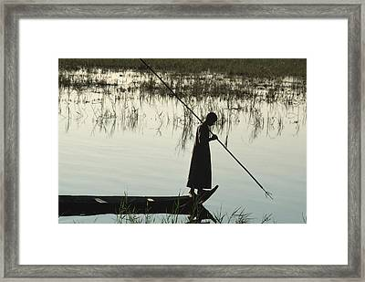 A Woman Stands At The End Of A Rowboat Framed Print by Lynn Abercrombie
