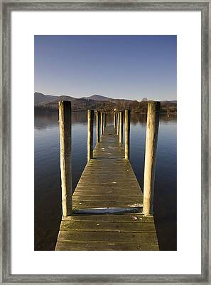 A Wooden Dock Going Into The Lake Framed Print by John Short