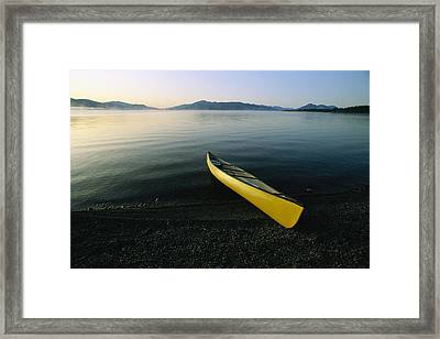 A Yellow Canoe On The Shore Of A Calm Framed Print by Michael Melford