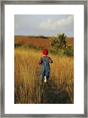 A Young Boy Walks On A Path Framed Print by Raul Touzon