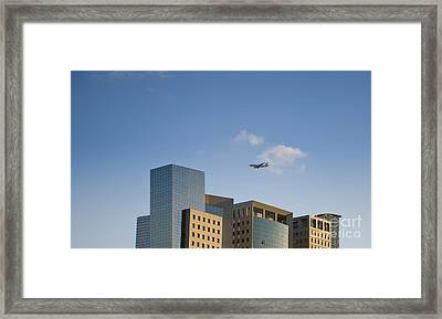 Airplane Flying Over Office Buildings Framed Print by Noam Armonn