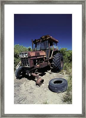 An Abandoned Tractor Rusts Away Framed Print by Jason Edwards