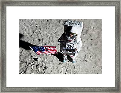 An Astronaut On The Surface Of The Moon Next To An American Flag Framed Print by Caspar Benson