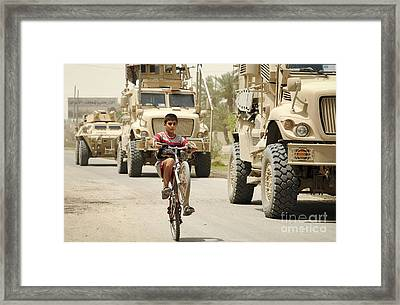 An Iraqi Boy Rides His Bike Past A U.s Framed Print by Stocktrek Images