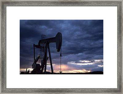 An Oil Rig Silhouetted At Sunset Framed Print by Joel Sartore