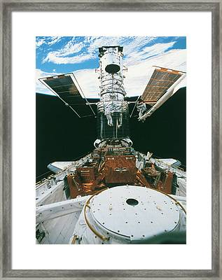 Astronauts Of The Space Shuttle Working On A Satellite In Space Framed Print by Stockbyte