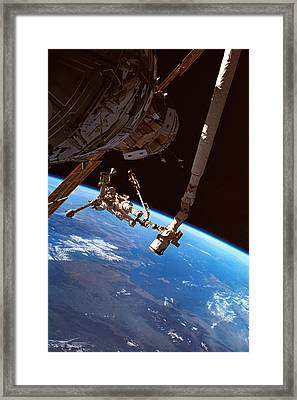 Astronauts Working On A Satellite In Space Framed Print by Stockbyte